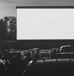 Grayscale photo of about 15 cars parked in front of a large drive through screen with a darkening sky at dusk in the background