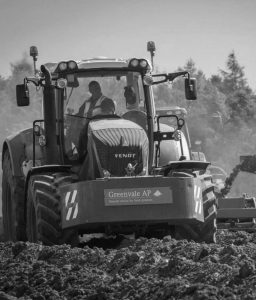"""Grayscale phot of a large piece of farming equipment with driver wearing a safety vest, the front bumper of the machinery with a sign that says, """"Greenvale AP, Natural choice for fresh potatoes"""""""