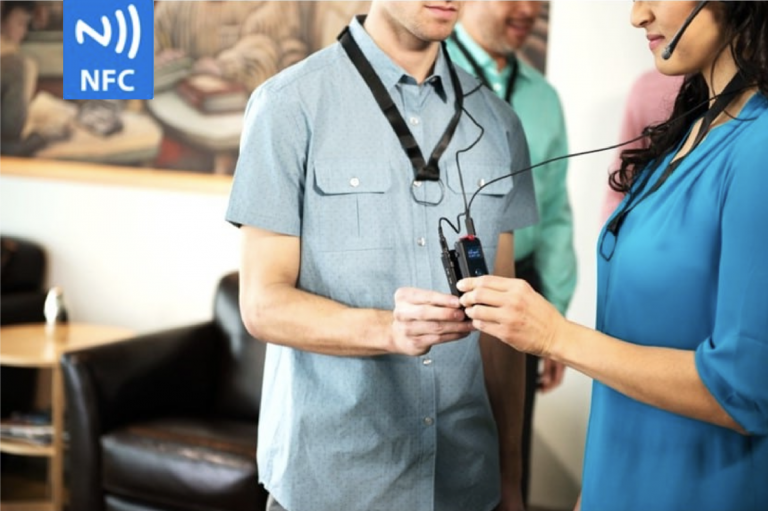 A man in a light blue short-sleeved button down shirt tapping his ListenTALK devices to pair it with a brunette woman in a blue blouse. There is also a logo in the top left-hand corner that says NFC and has waves on it. NFC stands for near-field communication.