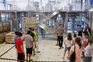 Tour of a brewery - a group of about 20, casually dressed, people wearing headphones, facing one guy dressed in black jeans and gray t-shirt, also wearing a headset with a microphone and pointing to something behind him.