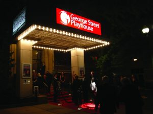 Front view of the George Street Playhouse building with attendees walking in.