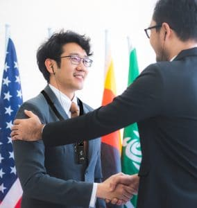 Business man shaking hands with a man in front of international flags.