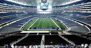 Wide view of an empty Dallas Cowboys stadium with a few players on the field