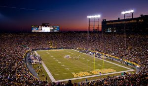 Outdoor football field and arena, Lambeau Field, at dusk, with players on the field and on the sidelines, fans in the arena, the lights are on and there is a large digital display at the end
