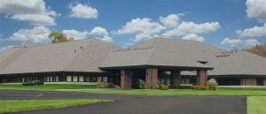 Large one story brown brick building with a covered drive-thru entrance, green grass, a black asphalt parking lot.