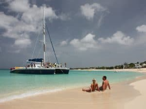 Middle aged couple sitting on a tropical beach admiring a sail boat coming in to shore.