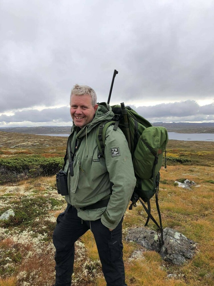 Halvard Eriksen smiling, standing outdoors in a beautiful landscape with clouds and mossy grass, with a green coat on, a heavy backpack, and his hunting rifle